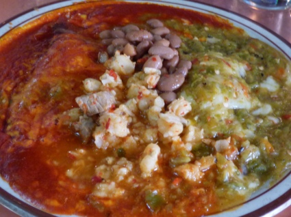 Blue corn wrapped cheese enchiladas with red and green sauce served with posole and beans.