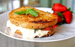 Grilled cheese sandwich with tomato and basil on sourdough bread.